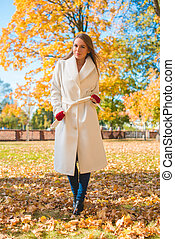 Stylish woman walking through an autumn park - Stylish...