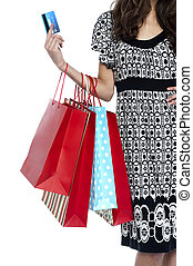 Stylish woman walking with shopping bags and credit card, ...