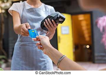 Stylish woman wearing nice bracelet paying for coffee by card