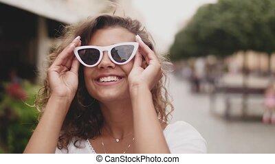 Stylish Woman Wearing Sunglasses Standing On City Street. Close up