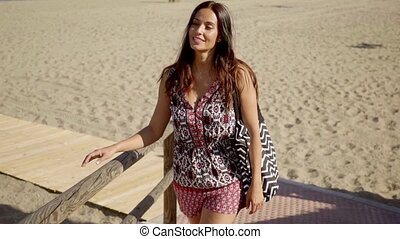 Stylish woman with a happy smile at the beach