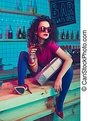 stylish woman with cocktail and boombox