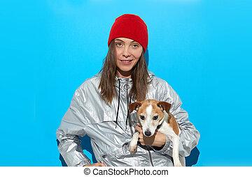 Stylish woman with dog in studio