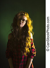 Stylish woman with long wavy hair wearing glasses