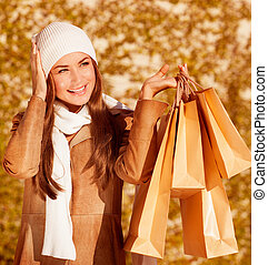 Photo of fashionable woman hold golden presents bag on yellow autumnal background, closeup portrait of cute stylish girl having fun outdoors, autumn seasonal sale, spend money concept
