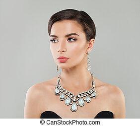 Stylish woman with short hair, makeup and diamond jewelry, fashion portrait