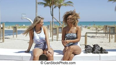 Stylish women chilling on coastline in sunshine - Confident...