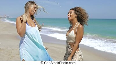 Stylish women walking on beach