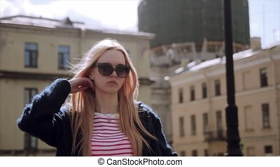 Stylish young beautiful blonde girl on a sunny day posing at sunny city street