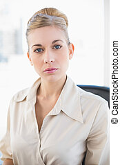 Stylish young blonde businesswoman looking at camera