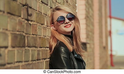 Stylish young blonde in sunglasses and black leather jacket near a brick wall on the street.