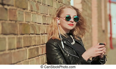 Stylish young blonde in sunglasses and leather jacket listening to music on bluetooth headphones in a mobile phone. Enjoy music. Background of a brick wall.