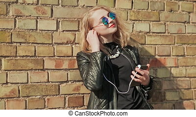 Stylish young blonde in sunglasses and leather jacket listening to music on bluetooth headphones in a mobile phone. Enjoy music. Spring. Background of a brick wall.