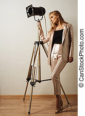 stylish young business woman in trousers and a jacket stands near a theatrical lantern