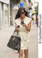Stylish young business woman texting
