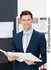 Stylish young businessman standing holding a large file in his hands as he smiles at the camera