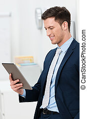 Stylish young businessman reading a tablet-pc