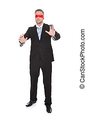 Stylish young businessman wearing a red blindfold stretching...