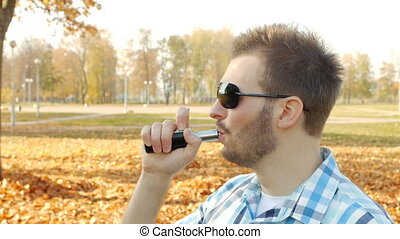 Stylish young caucasian guy in black glasses smokes vape on...
