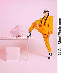 Stylish young female office worker in sunglasses with obsolete computer. Colored Neon light