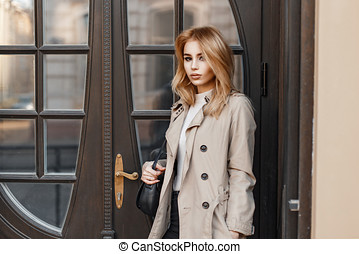 Stylish young girl in a coat stands near the vintage door