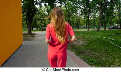 Stylish young girl in a red suit walking down the street