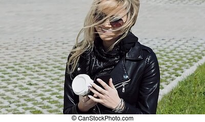 Stylish young girl on the street, in jacket and sunglasses -...
