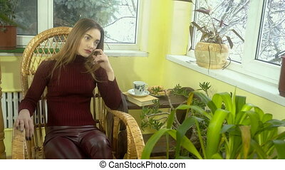Stylish young girl with beautiful make-up sitting in a wicker rocking chair and looking out the window