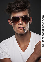 Stylish young man with cigarette between lips