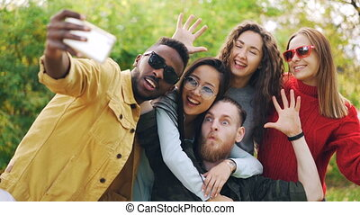 Stylish young people girls and guys are using smartphone to take selfie in park posing for camera and laughing. Students are wearing casual clothing and sunglasses.