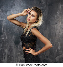 Stylish young woman in black lace top and skirt