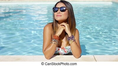 Stylish young woman in sunglasses and bikini standing in the...