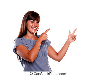 Stylish young woman looking at you and pointing up