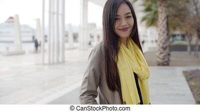 Stylish young woman on a waterfront promenade