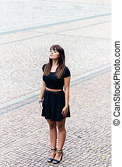 Stylish young woman standing on cobblestone