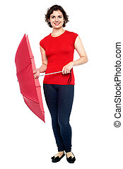Stylish young woman with an umbrella in hand