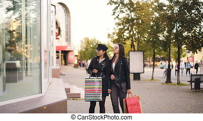 Stylish young women friends are walking along street holding...