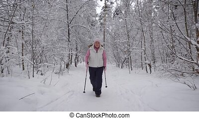 Stylishly dressed elderly woman is engaged in a new type of sports walking in winter snow-covered wood. Active pensioner spends his holiday in the fresh air.