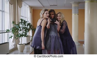 Stylishly dressed models made selfie on smartphone when one of them remind they need to rush to the fashion show. Silly funny girls running away in the direction of the door.