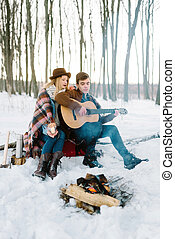 stylishly dressed young couple, sitting near the fire in the winter forest