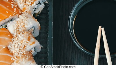 Stylishly laid sushi set on a black wooden background next...