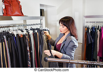 stylist chooses clothes in the store