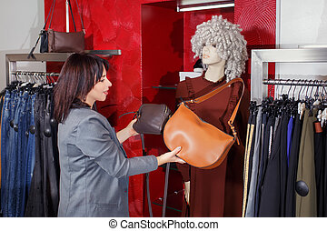 stylist chooses handbag in the store