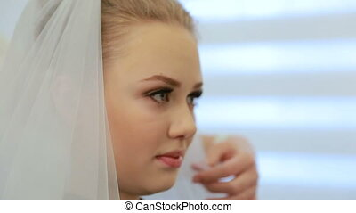 Stylist chooses the veil for future bride. Putting the bride's white veil on the hair of the bride.