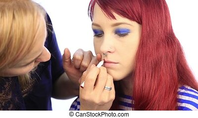 stylist draws the contour of the model's lips with a red pencil. make-up artist apply lipstick with brush on a woman's lips
