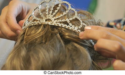 Stylist dresses crown on head of model. Close-up - Stylist...