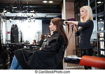 Stylist drying hair of a female client at beauty salon
