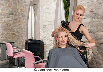 Stylist drying hair of female client at beauty salon. Young...