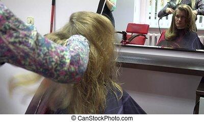 stylist drying hair with round brush. Girl before mirror. 4K
