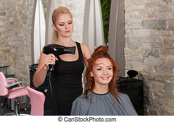 stylist drying redhead woman hair in salon. Young female ...